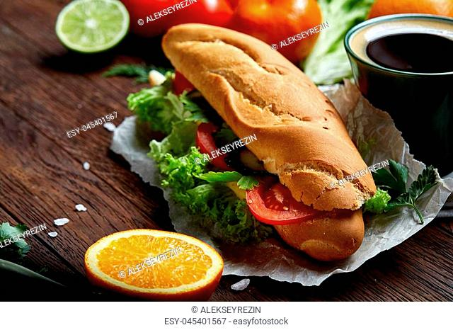 Fresh homemade sub sandwich with lettuce, tomatoes and cheese served with fresh tomatoes, cup of refreshing coffee on wooden plate over vintage wooden...