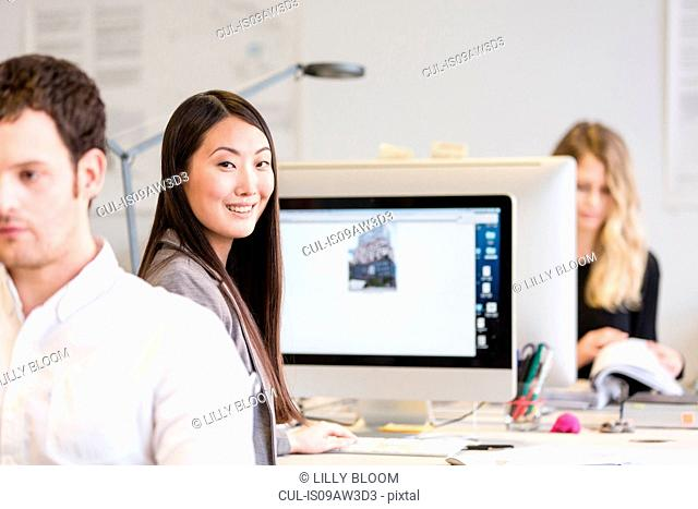Mid adult woman sitting at computer looking over shoulder at camera smiling