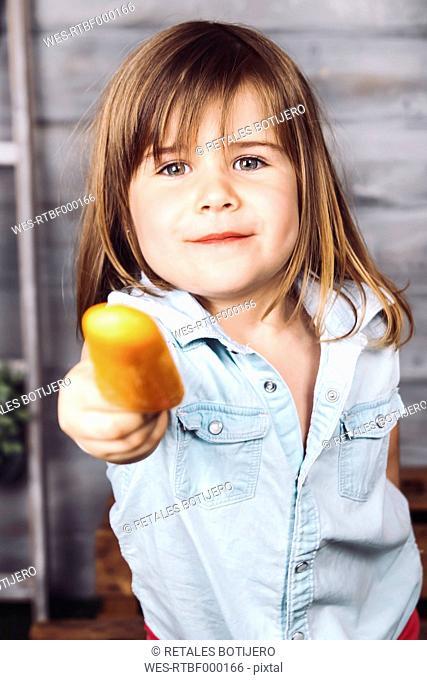 Portrait of little girl offering ice lolly