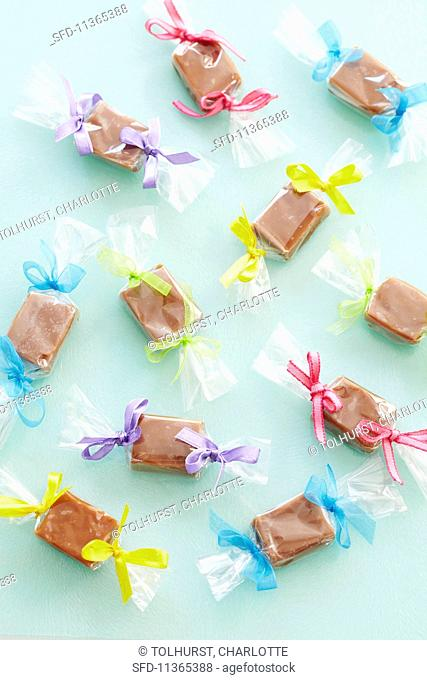Toffee bonbon wrapped in cellophane with coloured bows (seen from above)