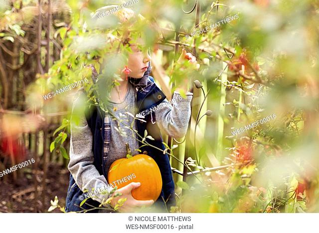 Boy holding pumpkin in garden