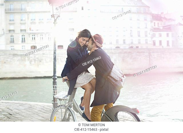 Couple hugging on bicycle along Seine River, Paris, France