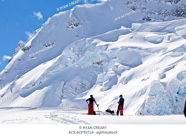 A backcountry skier and a splitboarder touring at Icefall Lodge, Canadian Rockies, Golden, BC