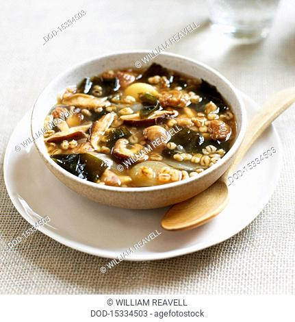 Bowl of soup containing barley, chestnuts, shiitake mushrooms, onions and wakame seaweed