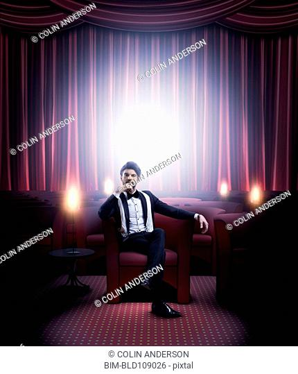 Hispanic man in tuxedo sitting in empty lounge