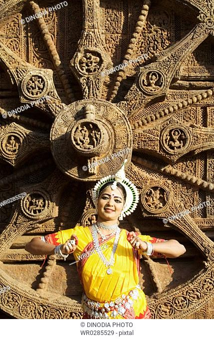 Odissi dancer strike pose re-enacts Indian myths such as Ramayana in front of Sun chariot world heritage Sun temple complex in Konarak , Orissa , India MR400