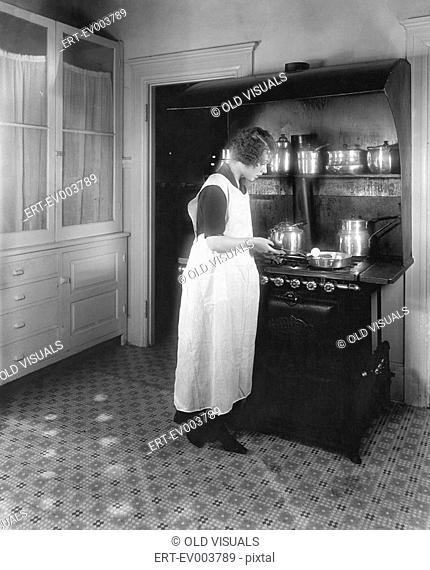 Woman cooking in kitchen All persons depicted are not longer living and no estate exists Supplier warranties that there will be no model release issues