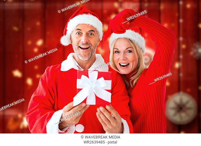 Portrait of happy couple in santa costume holding christmas gift