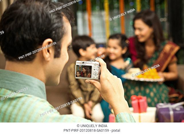 Man taking a picture of his family with a camera on Diwali