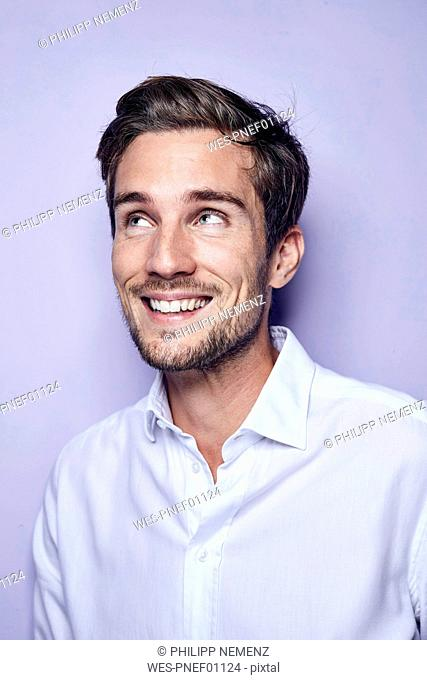 Portrait of laughing young man in front of purple background looking up
