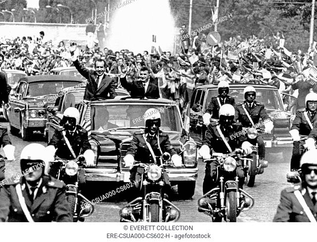 President Richard Nixon and President Nicolae Ceausescu wave to huge, flag-waving crowd during motorcade in Bucharest, Romania