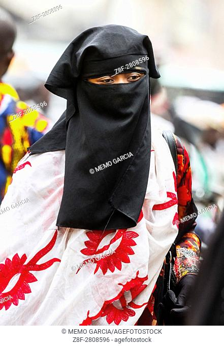 A young lady, muslim outfit, completely covered from head to foot, walking downtown in Bamako the Capital City of Maly/West Africa