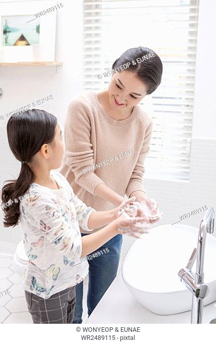 Loving mother and daughter washing hands together in bathroom