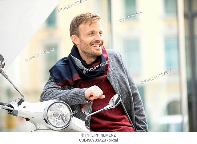 Mid adult man leaning against moped on city street