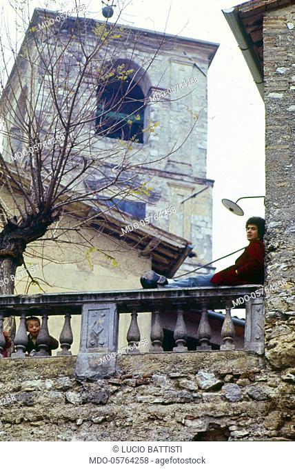 The Italian singer-songwriter Lucio Battisti in his hometown, sitting on a balustrade near a bell tower. Poggio Bustone, January 1969