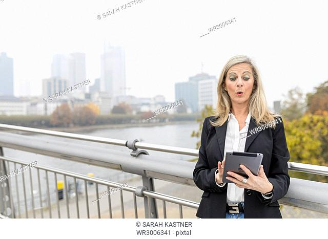 Businesswoman with tablet on a bridge