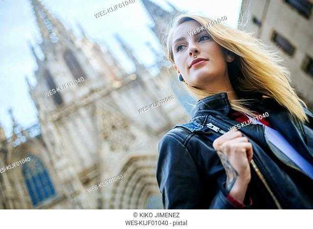 Spain, Barcelona, portrait of young woman with cathedral in the background