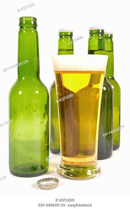 Glass of lager beer with green bottles