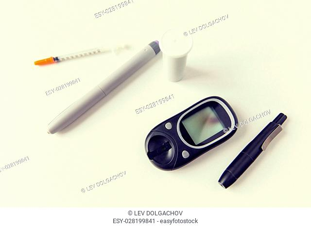 medicine, diabetes, medical tool and health care concept - close up of glucometer, insulin pen and syringe on table
