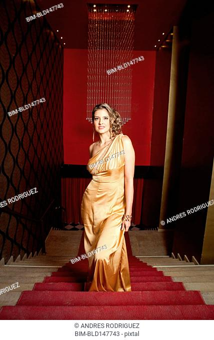 Glamorous Hispanic woman in evening gown standing on stairs