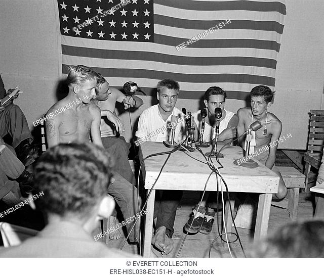 American POWs released during 'Operation Big Switch' being interviewed by the press. They display their camp mascot 'Oscar' a pet magpie at 'Freedom Village'