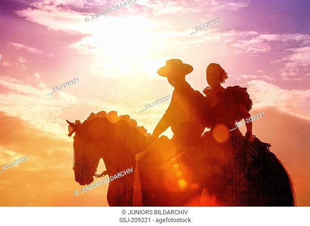 Lusitano. Couple in Spanish costume riding on a Feria, silhouetted against a dramatic sky. Germany