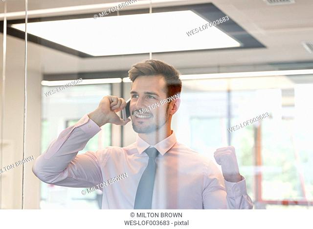 Young businessman in office looking through glass pane using smart phone