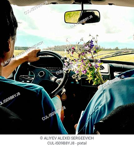 Man driving passenger with wild flowers, Ural, Sverdlovsk, Russia