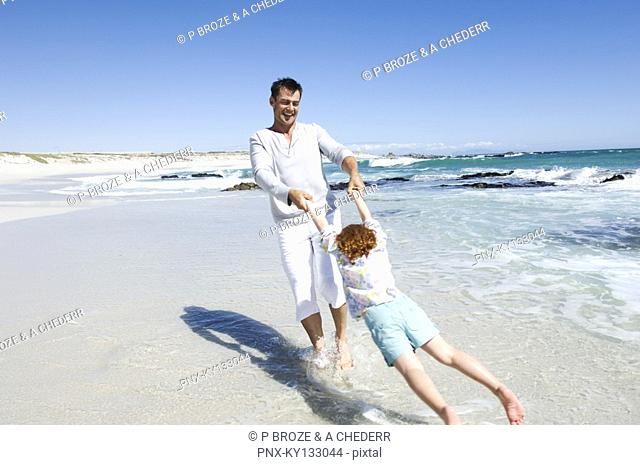 Father playing with daughter on the beach, outdoors