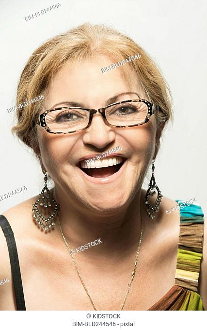 Close up of laughing woman with eyeglasses and earrings