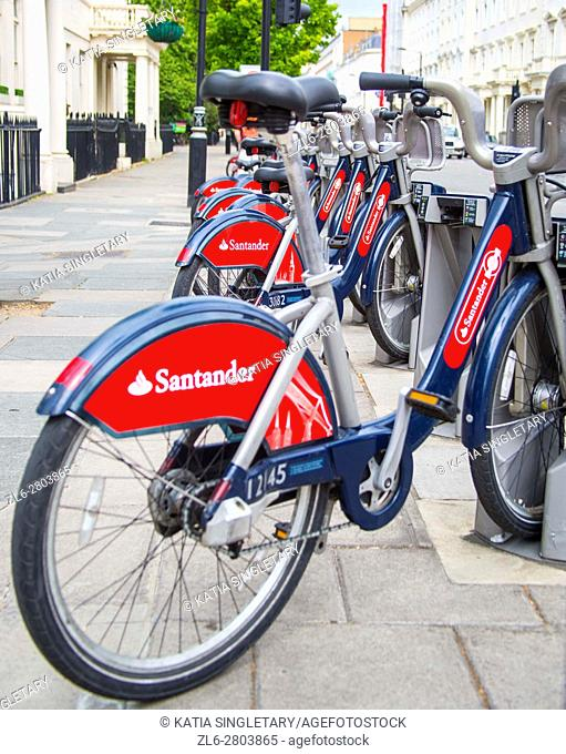 Bike to share in London in the capital of the UK. Red bicycles for rent for tourists in the big cosmopolitan city