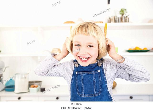 Portrait of cute girl in kitchen holding carrots to her ears