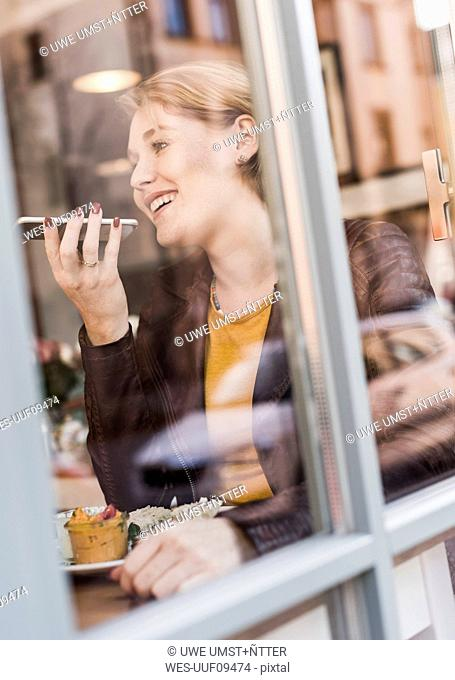 Young woman using cell phone in a cafe
