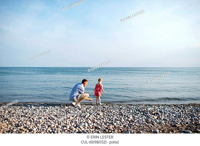 Mid adult man and daughter skimming stones at Lake Ontario, Oshawa, Canada