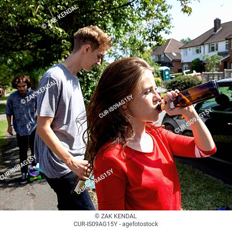 Friends drinking beer in street