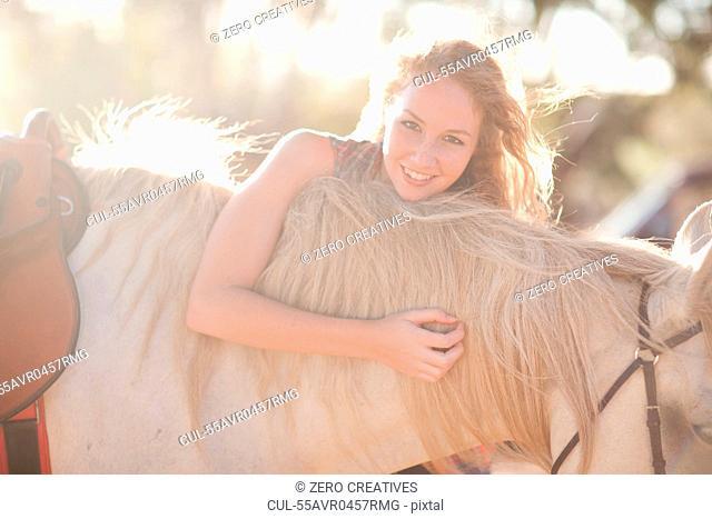 Young woman touching horse's man