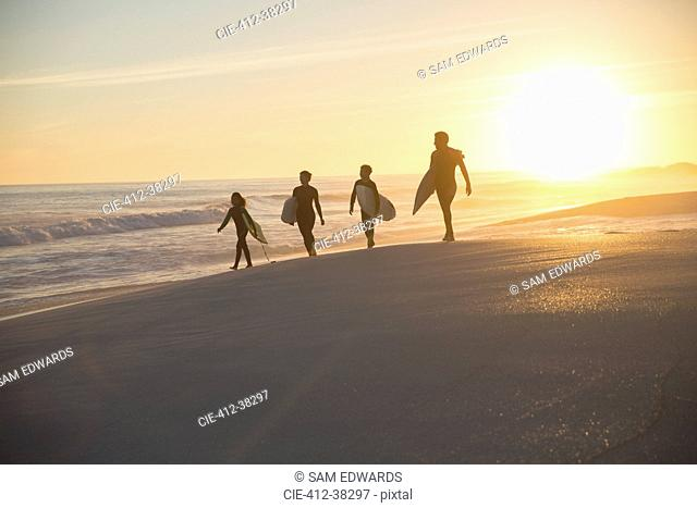 Silhouette family surfers walking with surfboards on sunny summer sunset beach