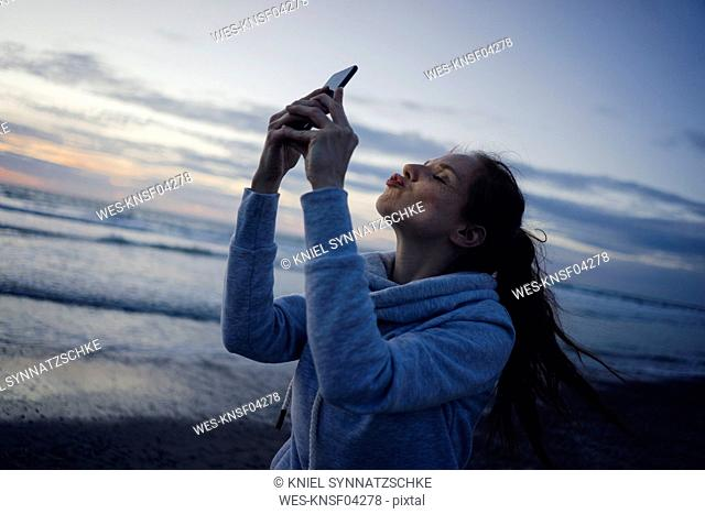 Woman using smartphone on the beach at sunset, sending kiss