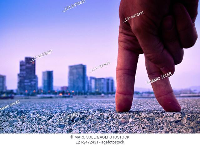 Spain, Catalonia, Barcelona, Close up of hand with city buildings in background at sunset
