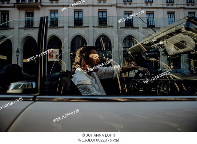 Man driving convertible in Munich, Bavaria, Germany
