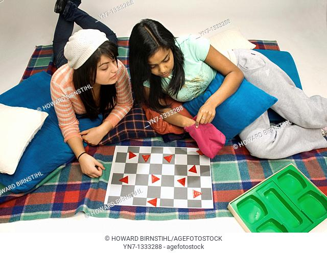 aerial view of two teenage girls setting up to play a board game
