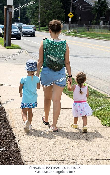 Young woman and two little girls walking by the street, Philadelphia, USA