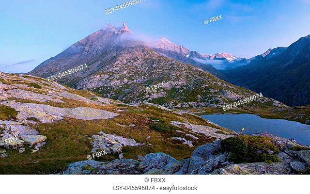 High altitude alpine lake in idyllic land with majestic rocky mountain peaks. Long exposure at dusk. Wide angle view on the Alps