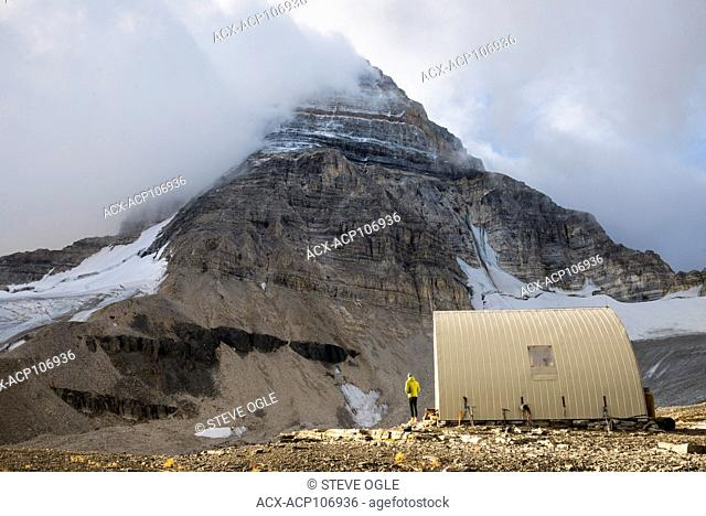 A climber scopes the summit while at the R.C. Hind hut below Mt. Assiniboine