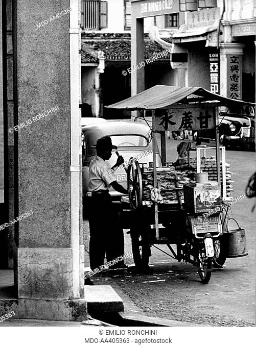 A pedlar in the street . A pedlar putting the food that he will sell in the street on his rickshaw. Malaysia, 1950s