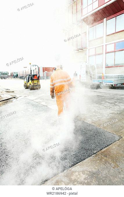 Manual worker laying asphalt at construction site