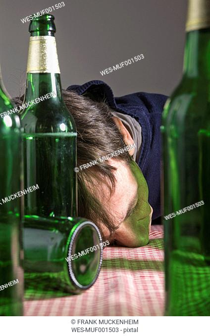Man lying on table surrounded by beer bottles