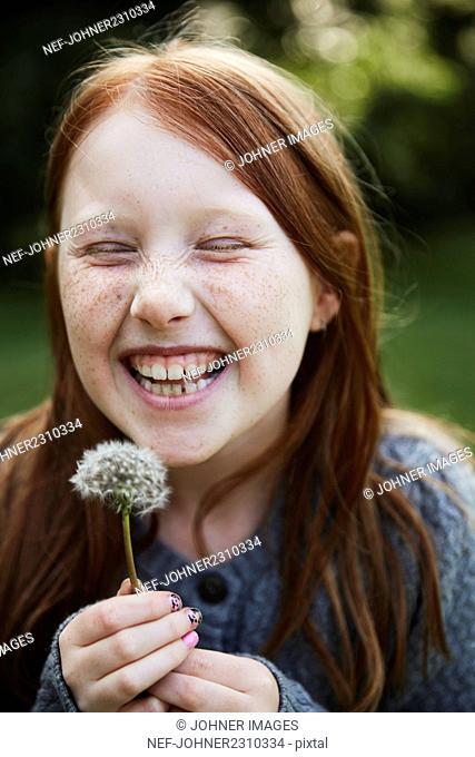 Portrait of girl holding dandelion