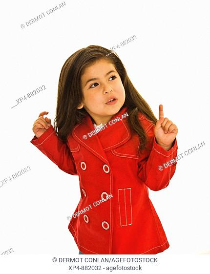 Four year old girl with long brown hair in red jacket with white buttons. She is looking off to camera right with her arms raised up and both index fingers...