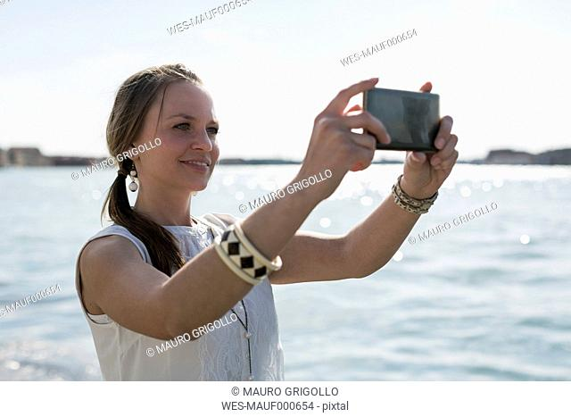 Italy, Venice, Tourist making a selfie with smart phone